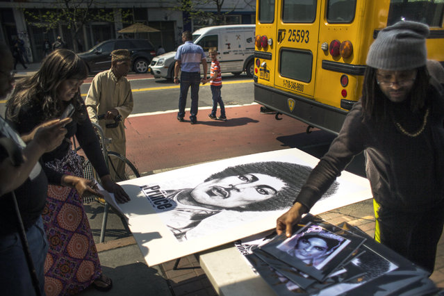 People buy posters and pictures of Prince outside of the Apollo Theatre in New York, Friday, April 22, 2016. (Photo by Andres Kudacki/AP Photo)