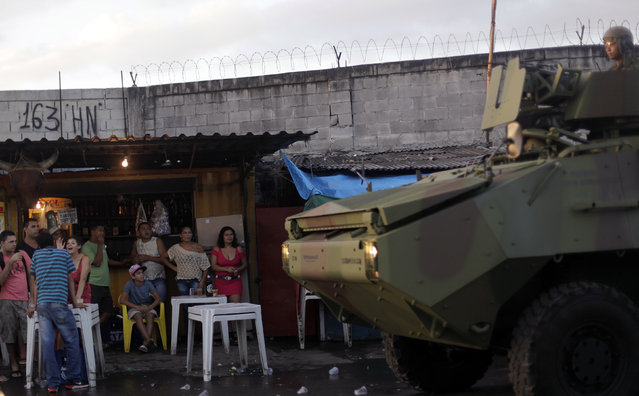 Residents watch as Brazilian Navy soldiers in an armoured vehicle patrol the Mare slums complex in Rio de Janeiro, April 5, 2014.(Photo by Ricardo Moraes/Reuters)