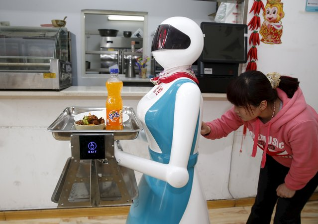 A woman input orders for a robot which works as a waitress in a restaurant in Xi'an, Shaanxi Province, China, April 20, 2016. (Photo by Reuters/Stringer)