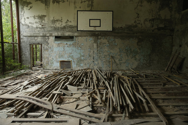 "Floorboards lie in the former basketball court under peeling walls at the abandoned ""Lazurna"" public swimming pools facility on September 30, 2015 in Pripyat, Ukraine. (Photo by Sean Gallup/Getty Images)"