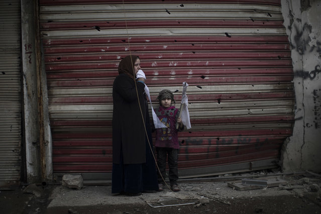 A girl stands with a woman holding a white flag to show they are civilians, as they flee their home during fighting between Iraqi security forces and Islamic State militants, on the western side of Mosul, Iraq, Monday, March 13, 2017. (Photo by Felipe Dana/AP Photo)
