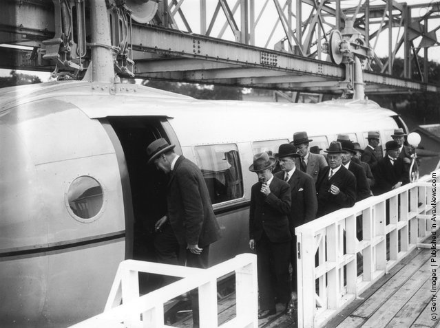 1930: The first load of passengers queuing for the Bennie Railplane in Glasgow; the inventor George Bennie is third in the queue. The streamlined cars are self propelled, driven by air screws in front and behind, and hang from a steel girder