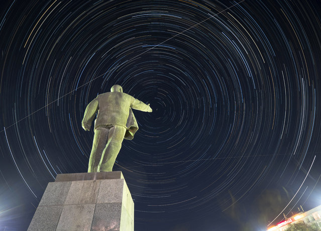 The International Space Station (ISS) moves along its orbit above at the Russian leased Baikonur cosmodrome, Kazakhstan, Thursday, July 18, 2019, with a statue of Soviet Union founder Vladimir Lenin in the foreground. Circular star tracks around the Polar Star and tracks of the ISS is the result of the camera multiple exposure with a total duration of two hours. The new Soyuz mission to the International Space Station (ISS) is scheduled on Saturday, July 20 with U.S. astronaut Andrew Morgan, Russian cosmonaut Alexander Skvortsov and Italian astronaut Luca Parmitano. (Photo by Dmitri Lovetsky/AP Photo)