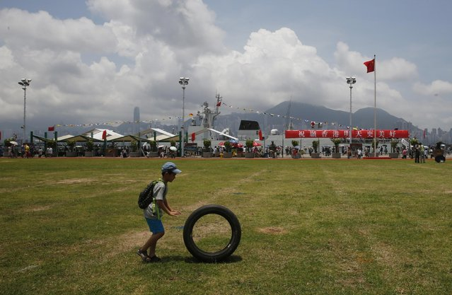 A boy plays with a tire at the open day of Stonecutter Island Navy Base of Chinese People's Liberation Army (PLA) in Hong Kong to mark the 18th anniversary of the Hong Kong handover to China in Hong Kong, Wednesday, July 1, 2015. (Photo by Kin Cheung/AP Photo)