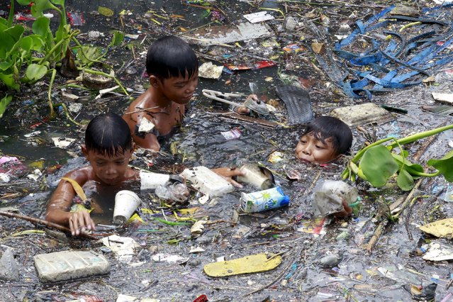 Boys sift through floating garbage as they collect recyclable materials in a polluted river at Navotas city, north of Manila, July 2, 2015. (Photo by Romeo Ranoco/Reuters)