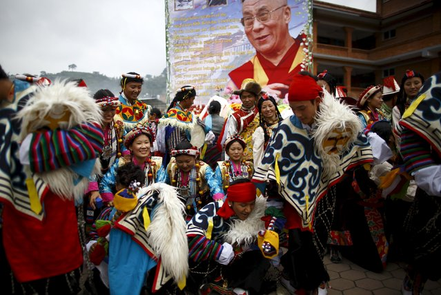 Tibetans dressed in traditional attire gather for pictures in front of the portrait of Dalai Lama during his 80th birthday celebration in Kathmandu July 6, 2015. (Photo by Navesh Chitrakar/Reuters)