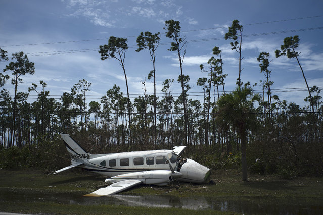 A broken plane lays on the side of a road in the Pine Bay neighborhood in the aftermath of Hurricane Dorian in Freeport, Bahamas, Wednesday, September 4, 2019. Rescuers trying to reach drenched and stunned victims in the Bahamas fanned out across a blasted landscape of smashed and flooded homes Wednesday, while disaster relief organizations rushed to bring in food and medicine. (Photo by Ramon Espinosa/AP Photo)