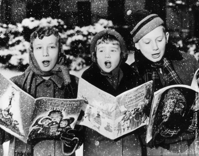 1957: Three young carol singers give their rendering of a Christmas song in the falling snow
