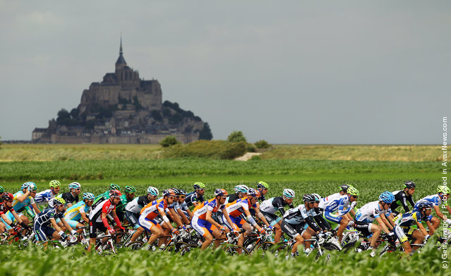 The peloton passes by Le Mont-Saint-Michel at the start of stage six of the 2011 Tour de France from Dinan to Lisieux