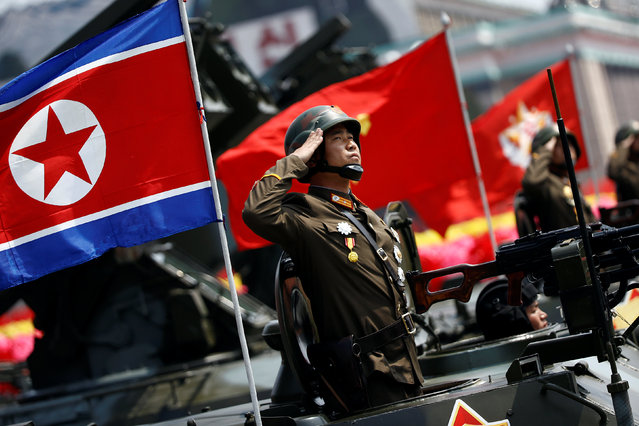 A soldier salutes from atop an armoured vehicle as it drives past the stand with North Korean leader Kim Jong Un during a military parade marking the 105th birth anniversary of country's founding father Kim Il Sung, in Pyongyang April 15, 2017. (Photo by Damir Sagolj/Reuters)