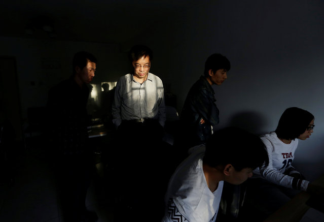 Wu Yaxiong (2nd L), CEO of N-Wei (Beijing) Technology Company Limited, stands with his programmers in an apartment which he rents as office and employees' dormitory, in Beijing, China, April 22, 2016. (Photo by Jason Lee/Reuters)