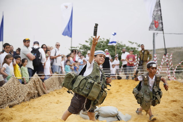 An Israeli boy dresses wearing a military vest  throws a mock granade during a traditional military weapon display to mark the 66th anniversary of Israel's Independence at the West Bank settlement of Efrat on May 6, 2014 near the biblical city of Bethlehem. (Photo by Gali Tibbon/AFP Photo)