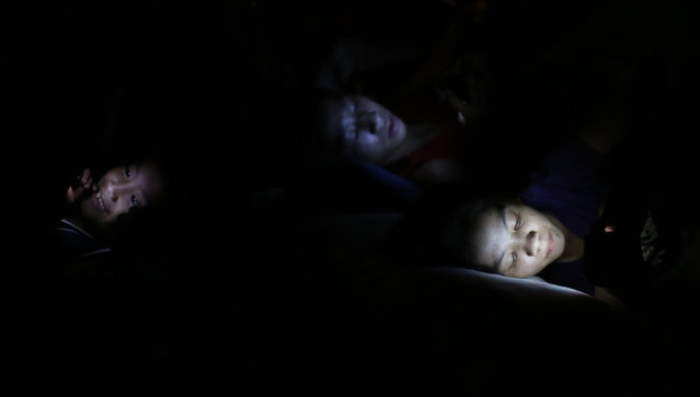 Flood victims use electronic devices as they rest at an evacuation center after their homes were inundated as Tropical storm Fung-Wong battered the Philippine capital Manila September 19, 2014. (Photo by Erik De Castro/Reuters)