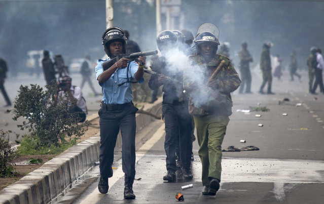 Riot police fire tear gas toward demonstrators as they flee, during a protest in downtown Nairobi, Kenya Monday, May 16, 2016. (Photo by Ben Curtis/AP Photo)