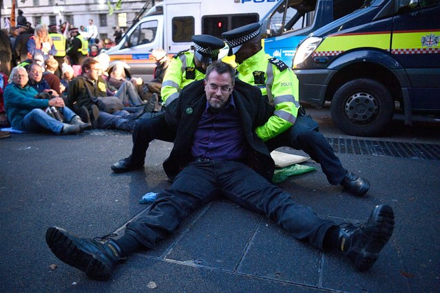 Extinction Rebellion climate change protesters are arrested as they demonstrate in Whitehall in London, Britain, 08 October 2019. Global climate movement Extinction Rebellion announced climate change protests and blockades worldwide for two weeks starting 07 October. (Photo by Neil Hall/EPA/EFE)