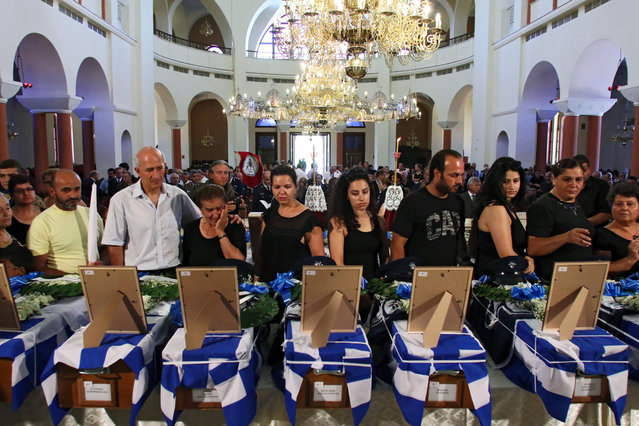 People mourn during a funeral service for 17 people whose remains have been found in a mass grave and identified through the DNA method, during a memorial service marking the 41st anniversary of the military coup in Cyprus, held for those killed during the uprising, at Sofia tou Theou Church, in Nicosia, Cyprus, July 15, 2015. In 1974, after clashes between the Greek Cypriot and Turkish Cypriot communities, Greek Cypriot nationalists and a Greek military junta attempted to unify the country with Greece. (Photo by Katia Christodoulou/EPA)