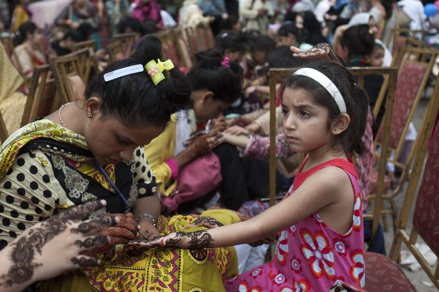 Pakistani beauticians paint the hands of customers with henna ink ahead of the Muslim Eid al-Fitr holiday to mark the end of the holy fasting month of Ramadan, Friday, July 17, 2015, in Karachi, Pakistan. (Photo by Shakil Adil/AP Photo)