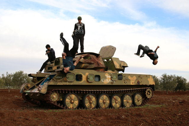 Muhannad al-Kadiri (R),18, and Ibrahim Eid, 16, demonstrate their Parkour skills over a military vehicle in the rebel-held city of Inkhil, west of Deraa, Syria, February 4, 2017. (Photo by Alaa Al-Faqir/Reuters)