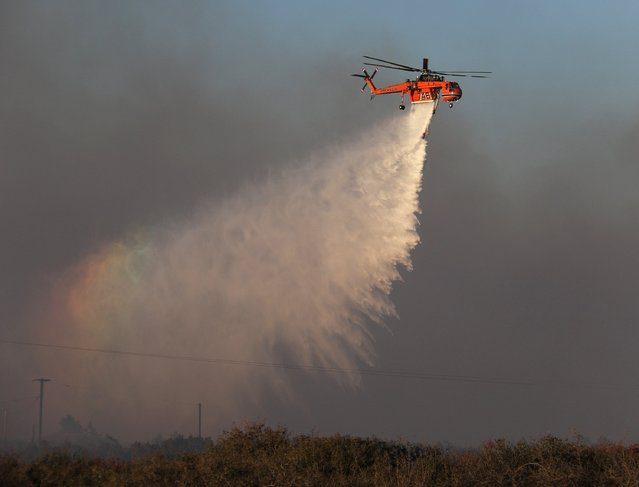 A sky crane helicopter makes a water drop at the North Fire near Phelan, California July 17, 2015. (Photo by Gene Blevins/Reuters)