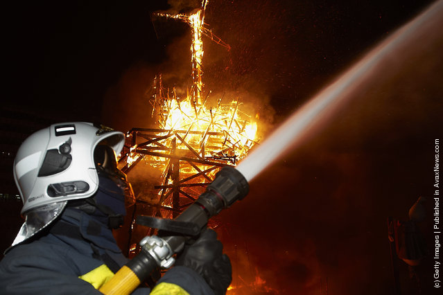 A fireman sprays water while a combustible 'Ninot' caricature burns in the background during the last day of the 'Fallas' festival on March 19, 2012 in Valencia, Spain