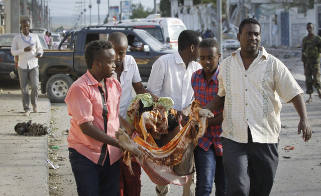 Somalis carry away the body of a person who was killed in a suicide car bomb attack in the capital Mogadishu, Somalia Sunday, July 26, 2015. Somali police officer says a suicide car bomber has rammed his car into the protective perimeter outside a well-known hotel in the Somali capital Sunday, killing at least four people. (Photo by Farah Abdi Warsameh/AP Photo)