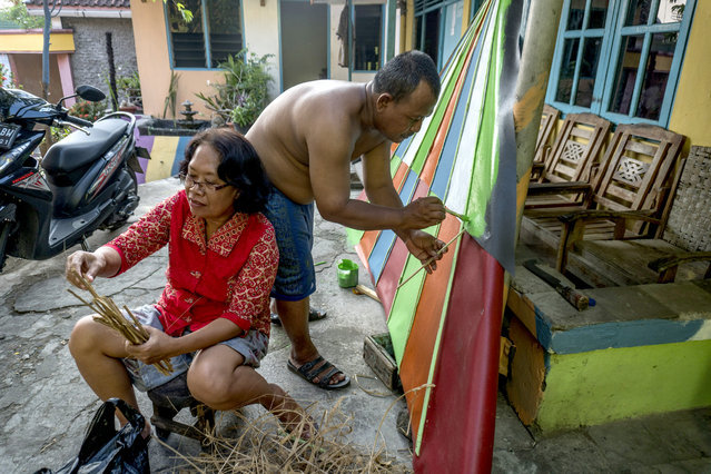"""This picture taken on May 23, 2017 shows villagers painting part of their homes following a major makeover of their Indonesian hamlet dubbed """"the rainbow village"""" in Semarang, central Java, that has become an internet sensation and attracting hordes of visitors. (Photo by Suryo Wibowo/AFP Photo)"""