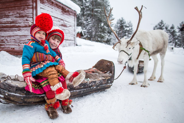 """""""Sami Children"""". The Samis, the indigenous people of Scandinavia, traditionally are reindeer herders. The Jokkmokk Winter Market, now going for more than 400 years, is a traditional festival and popular meeting place for the Sami people. Here, a charming and vivacious Sami girl pulls her brother onto her lap as he tries to wander off on his own. The wooden sleigh was later pulled by reindeers herded by her family and paraded through the market streets. Photo location: Jokkmokk, Swedish Lapland. (Photo and caption by Joyce Le Mesurier/National Geographic Photo Contest)"""