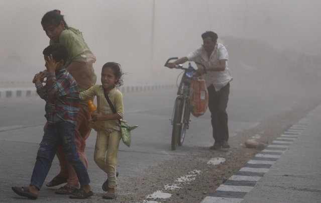 An Indian woman walks with two children, as one of them cries during a powerful dust storm  in Jammu, India, Monday, June 16, 2014. (Photo by Channi Anand/AP Photo)
