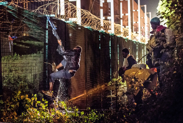A migrant climbs a security fence of a Eurotunnel terminal in Coquelles near Calais, northern France, on July 30, 2015. One man died on July 29 in a desperate attempt to reach England via the Channel Tunnel as overwhelmed authorities fought off hundreds of migrants, prompting France to beef up its police presence. (Photo by Philippe Huguen/AFP Photo)
