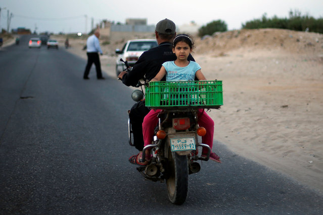 A Palestinian girl rides a motorcycle with her father on a street in the central Gaza Strip May 16, 2016. (Photo by Suhaib Salem/Reuters)