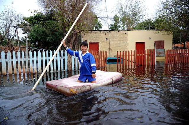 A child navigates on a makeshift raft in a flooded neighborhood of Asuncion, on July 2, 2014. Heavy rains have caused flooding across the country, killing at least one person and affecting some 30,000 familes in the Paraguyan capital and 200.000 across the country, according to official sources. (Photo by Norberto Duarte/AFP Photo)