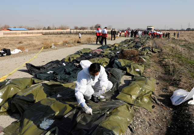 Passengers' bodies in plastic bags are pictured at the site where the Ukraine International Airlines plane crashed after take-off from Iran's Imam Khomeini airport, on the outskirts of Tehran, Iran on January 8, 2020. (Photo by Nazanin Tabatabaee/WANA (West Asia News Agency) via Reuters)