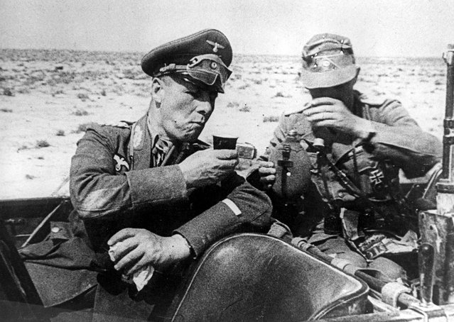 Field Marshal Gen. Erwin Rommel, commander of the German Afrika Korps, drinks out of a cup with an unidentified German officer as they are seated in a car during inspection of German troops dispatched to aid the Italian army in Libya in 1941