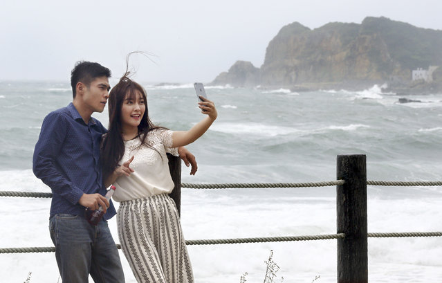 "A couple takes a ""selfie"" photograph in front of the crashing waves from Typhoon Soudelor off the coast of  Keelung, northeastern Taiwan, Friday, August 7, 2015. Soudelor is expected to bring heavy rains and strong winds to the island late Friday with winds speeds over 170 km per hour (100 mph) and gusts over 200 km per hour (120 mph) according to Taiwan's Central Weather Bureau. (Photo by Wally Santana/AP Photo)"