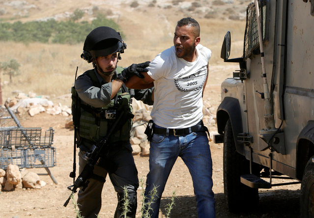 An Israeli border policeman detains a Palestinian man as Israeli troops demolish sheds belonging to Palestinians near the West Bank village of Yatta, south of Hebron June 19, 2016. (Photo by Mussa Qawasma/Reuters)
