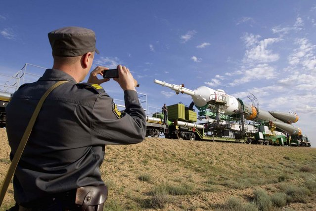 A policeman takes a picture of the Soyuz TMA-04M spacecraft during transportation to its launch pad at the Baikonur cosmodrome May 13, 2012
