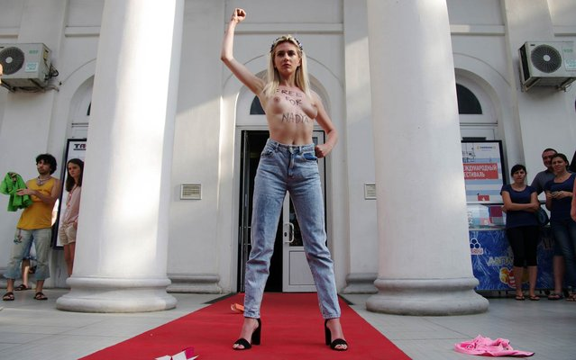 """A topless FEMEN activist bearing the inscription """"Free for Nadya"""" raises her fist as she shouts slogans during a demonstration in the southern Ukrainian city of Odessa on July 14, 2014, to demand to free Ukrainian military pilot Nadya Savtchenko (unseen). Savtchenko was captured on July 9 by pro-Russian militants in the east of the country and sent to Russia. (Photo by Alexey Kravtsov/AFP Photo)"""