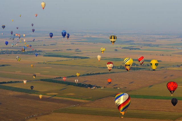 Hot air balloons fly during the 19th FAI Hot Air Balloon European Championship in Debrecen, 226 kms east of Budapest, Hungary, August 12, 2015. Hundred and two contestants of twenty-three countries participate in the event through August 18. (Photo by Zsolt Czegledi/EPA)