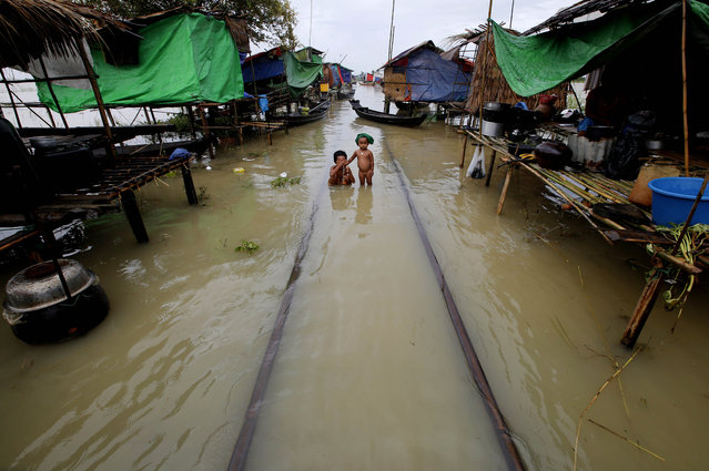 Children take a bath in floodwaters at a temporary shelter where victims of flooding gather in Kyaung Gone township of Ayeyarwaddy Region, Myanmar, August 13, 2015. Myanmar's government warned low-lying regions to expect even more flooding after heavy rainfall brought havoc to higher areas further north. (Photo by Lynn Bo Bo/EPA)