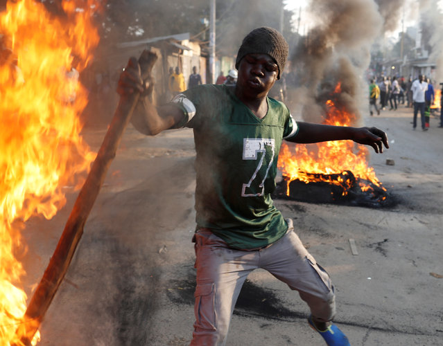 A supporter of opposition leader Raila Odinga sets up flaming tire barricade in Kibera slum in Nairobi, Kenya, August 9, 2017. (Photo by Goran Tomasevic/Reuters)