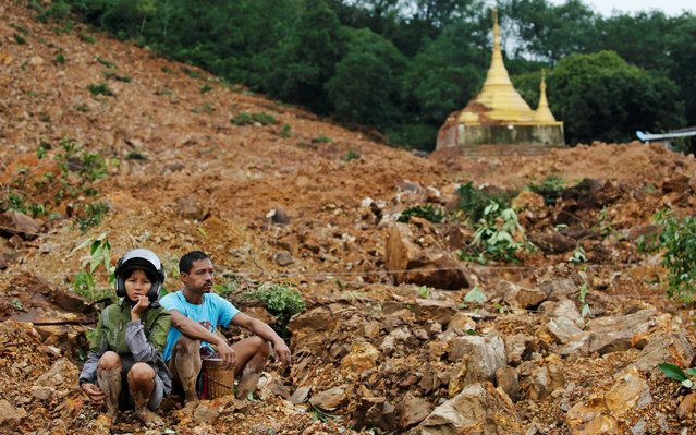 Residents and survivors sit at the site of a landslide in Mottama, Mon state, Myanmar, August 10, 2019. (Photo by Ann Wang/Reuters)