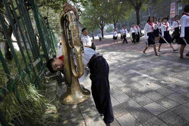 A North Korean student cleans his tuba ahead of a parade to celebrate the anniversary of the Korean war armistice agreement, Sunday, July 27, 2014, in Pyongyang, North Korea. (Photo by Wong Maye-E/AP Photo)