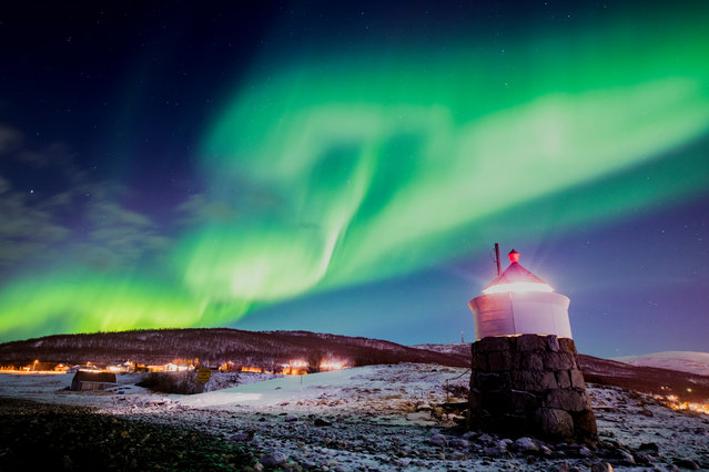 Aurora borealis or northern lights are visible in the sky above a lighthouse to the village of Strand near Tromso in northern Norway, 22 February 2018. Aurorae are caused by the interaction between energetic charged particles from the sun and gas molecules in the upper atmosphere of the earth, about 100 kilometres up. Streams of charged particles, called solar winds, flow out into space continuously from the sun at speeds of 400 to 500 kilometers per second. On reaching earth, the charged particles are drawn by earth's magnetic field to the poles, where they collide with gas molecules in the upper atmosphere, causing them to emit light. (Photo by Martial Trezzini/EPA/EFE)