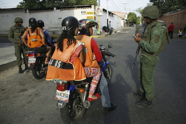 Venezuelan soldiers check the identity cards of people at a checkpoint close to the border with Colombia, as part of a special deployment, at San Antonio in Tachira state, Venezuela August 22, 2015. Venezuela's closure of two border crossings with Colombia hurts innocent people, Colombia's President Juan Manuel Santos said on Saturday, adding that he hoped to speak to his Venezuelan counterpart Nicolas Maduro to find a solution. (Photo by Carlos Eduardo Ramirez/Reuters)