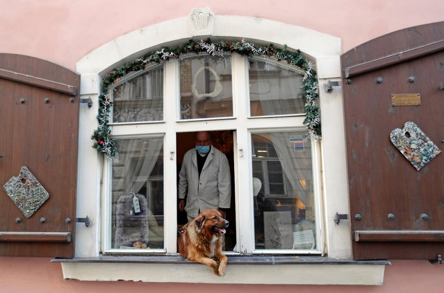 A man wearing a face mask and his dog look out of a window as the spread of the coronavirus disease (COVID-19) continues in Prague, Czech Republic, March 24, 2020. (Photo by David W. Cerny/Reuters)