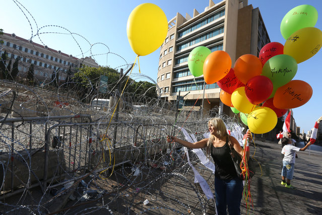 A Lebanese anti-government protester hangs a balloon on barbed wire in front the government building, during a demonstration against the trash crisis and government corruption, in downtown Beirut, Lebanon, Saturday, August 29, 2015. Hundreds of people began gathering Saturday amid tight security in downtown Beirut, ahead of a major rally that is expected to be the largest of protests that began last week. (Photo by Bilal Hussein/AP Photo)