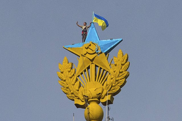 """A man takes a """"selfie"""" as he stands with a Ukrainian flag on a Soviet-style star re-touched with blue paint so it resembles the yellow-and-blue national colours of Ukraine, atop the spire of a building in Moscow August 20, 2014. Russian police said on Wednesday they had charged four young people with vandalism after they climbed to the top of a Moscow skyscraper and briefly attached a Ukrainian flag to its spire. (Photo by Ilya Varlamov/Reuters)"""