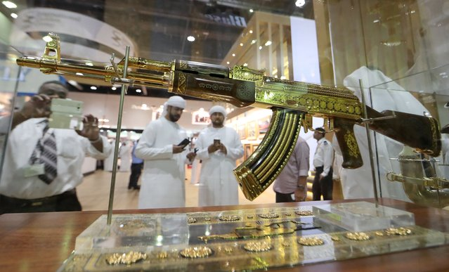A picture taken on September 14, 2017 shows Emirati men using their cell-phones to take pictutres of an ornamented gold-plated Kalashnikov AK-47 assault rifle on display at the Arabian Saluki beauty contest as part of the Abu Dhabi International Hunting and Equestrian exhibition (ADIHEX) in the UAE capital Abu Dhabi. (Photo by Karim Sahib/AFP Photo)