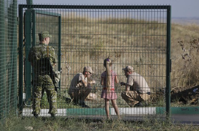 Drivers of trucks from the Russian aid convoy have a break in the Russian inspection zone inside a border control point with Ukraine in the Russian town of Donetsk, Rostov-on-Don region, Russia, Thursday, August 21, 2014. (Photo by Sergei Grits/AP Photo)