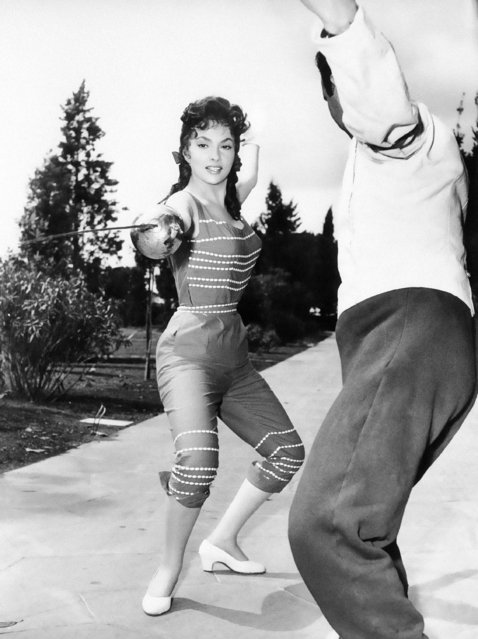Italian film star Gina Lollobrigida practices fencing under guidance of an instructor during a day off from her filming in Rome, June 3, 1955. She is also taking instruction in gymnastics for relaxation and to help keep a firm control over her famous figure. (Photo by AP Photo)